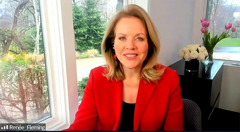 A smiling Renee Fleming wearing a red blazer speaks from her home.