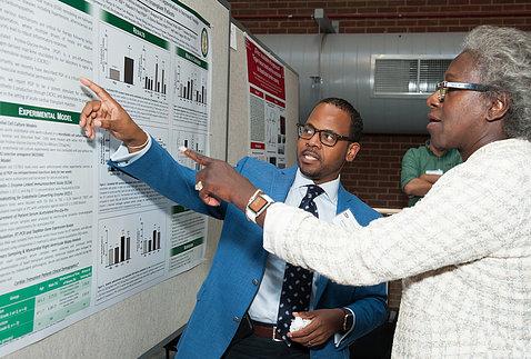 Gesturing toward a poster, black male scientist talks with black female scientist.