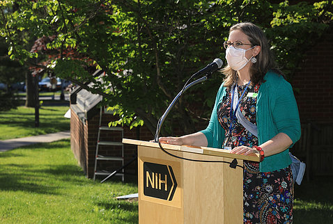 Dr. McCormick-Ell speaks at a podium while wearing a mask