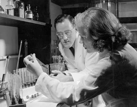 A researcher holds a vial of insulin as another researcher looks on, surrounded by vials in the lab.