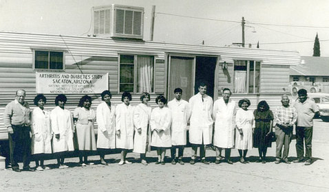 A black-and-white photo shows a group standing in front of a trailer.