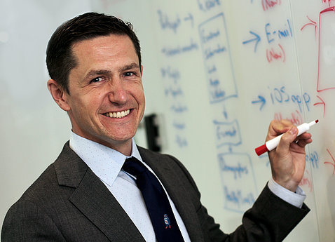 A smiling Shaw stands holding a marker up to a dry-erase board.