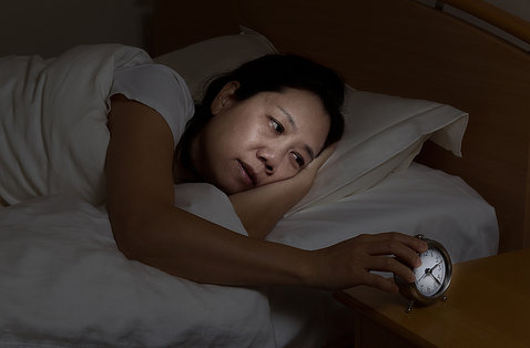A woman lies awake in bed looking sleepily at alarm clock on nightstand.