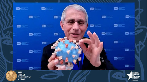 Dr. Fauci, holding a 3-dimensional model of the SARS-CoV-2 virus, pinches one of the orange spikes.