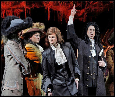 Austin in coattails and a long, curly-haired wig points a finger to the sky as he sings with 3 others in the troupe..