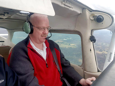 Dr. Michael Proschan, wearing headphones and mic, looks to be piloting a plane