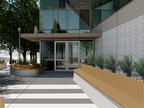 A crosswalk with a long wooden bench lead up to the modern, glass building.