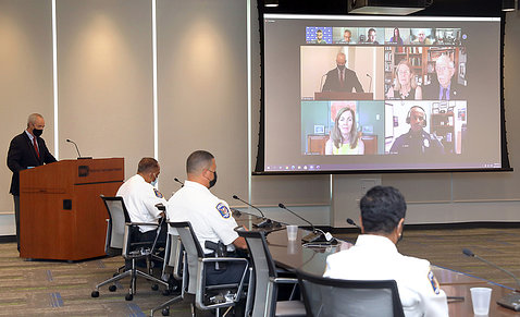 Male speaker at podium in conference room with uniformed officers seated around table looking at projector screen