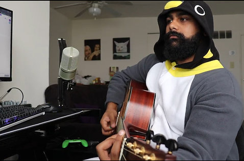 Shaikh, dressed in a hoodie, sits in his room strumming his guitar in front of a microphone and keyboard.