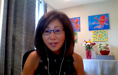 NICHD's Sonia Lee speaks on videocast from her home, with colorful artwork behind her.