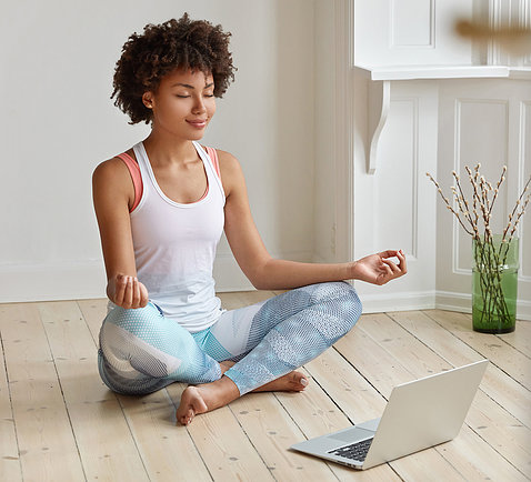 A young Black woman sits on the floor cross-legged, with palms up, fingertips touching, meditating in front of her laptop.