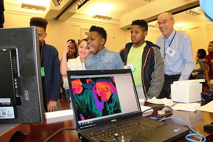 Students react as an infrared camera reveals heat radiating from their skin, also shown on the laptop monitor