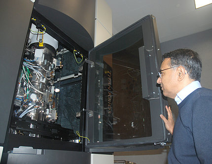 Dr. Subramaniam looks inside his EM machine.