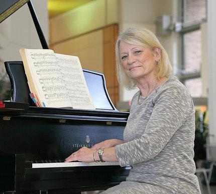 Woman at piano smiles, turned toward camera.