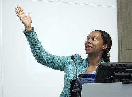 Lash gestures up toward slide as she speaks from behind podium.