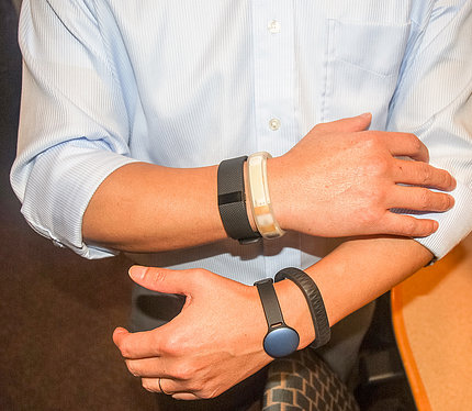 Scientist wearing several trackers holds up both arms to demonstrate the devices.