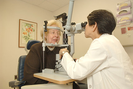 Chew examines a patient's eyes using a device
