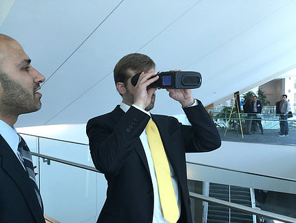 Attendee holds device up to his eyes.