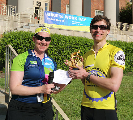 Man accepting trophy from woman