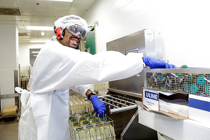 Man in labcoat, cap and gloves handles research materials and equipment.