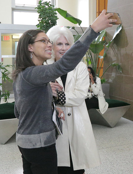 An NIH'er holds up her cell phone to take a photo of herself next to Rehm in the CC atrium.