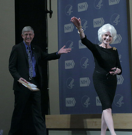 Rehm waves as she walks on stage, with a smiling Dr. Collins following behind.