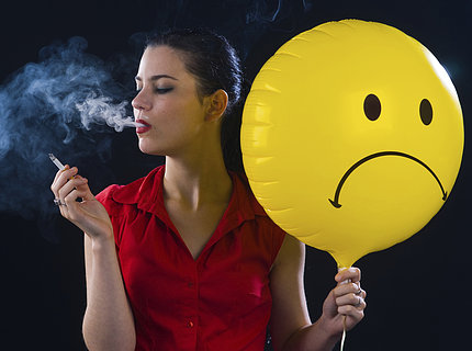 A woman blows smoke cloud and holds cigarette in one hand, a yellow, frowning-face balloon in the other