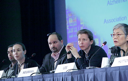 Five people seated behind microphones at panel table