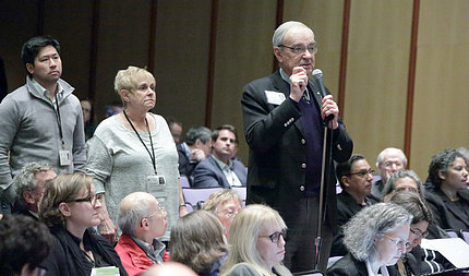 Several people from the audience line up at the aisle microphone to ask questions.