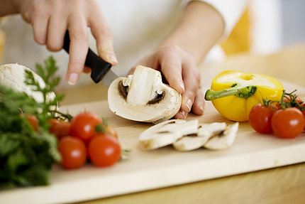 close-up view of hands holding large mushroom being sliced with cherry tomatoes in foreground and half yellow bell pepper alongside