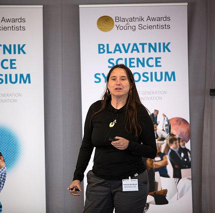 Roll-Mecak stands in front of Blavatnik Science Symposium banner