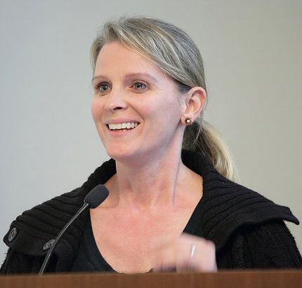 Lora Kutkat speaks at podium