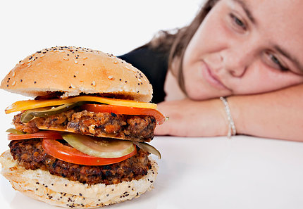 A girl rests her head on the table looking longingly at a large burger