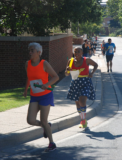 Woman dressed as Wonder Woman, in red, white & blue, running