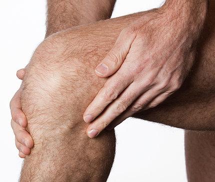 A man rubs his aching knee