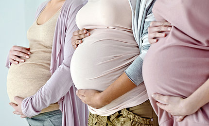 Three women place hands on their pregnant bellies.