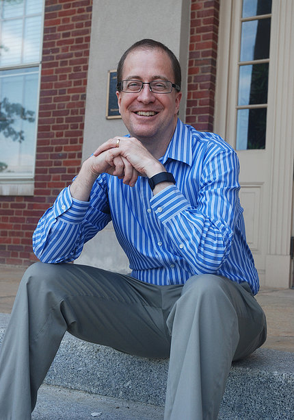 A smiling Eric Dishman sits outside Bldg. 1.