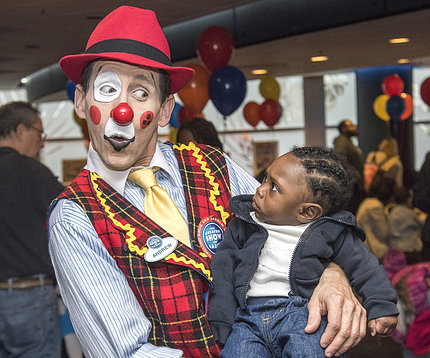 Circus clown cradles astonished young child.