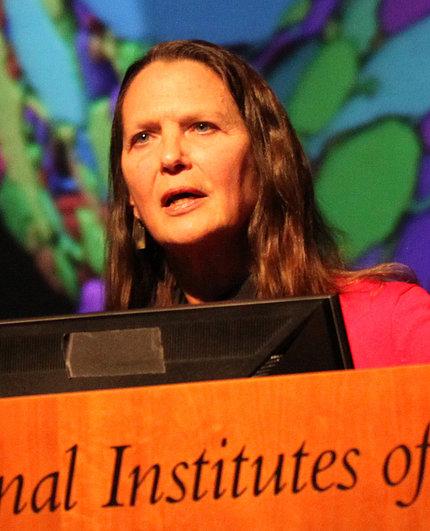 Dr. Hollis Cline speaks at podium in front of colorful slide