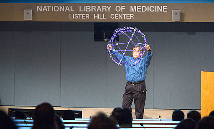 Loo holds up a ball constructed of strings of light.