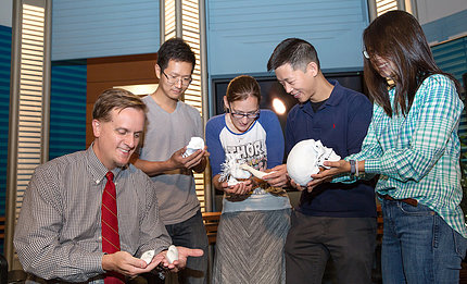 Five people examine the anatomical models they hold in their hands.