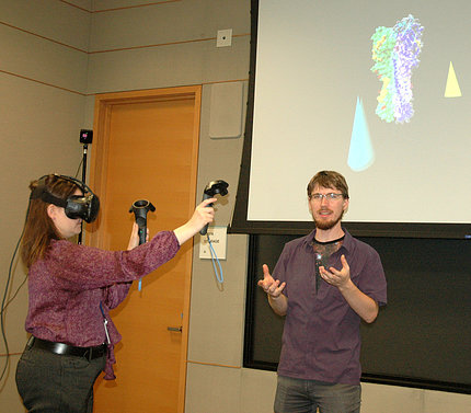 Scientist wears virtual reality goggles.