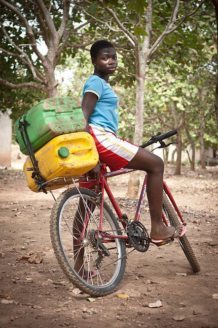 Woman uses bike to haul water.
