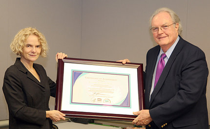 Dr. Volkow presents certificate to Dr. Johnston.