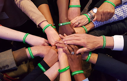 A dozen arms extended, each wearing a green wristband, with palms down, hands stacked
