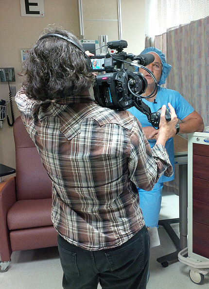 In blue scrubs, NHLBI's Dr. Tisdale talks on camera outside operating room in Clinical Center