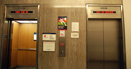 """A pair of elevators in Building 31, one of which displays sign above, """"Not in service."""""""