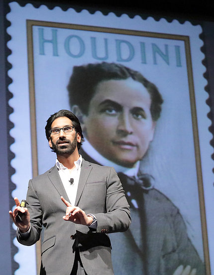 Pittampalli stands in front of a slide featuring a stamp of Houdini