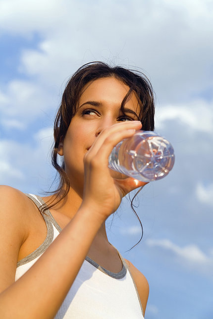 Young woman sipping from bottled water