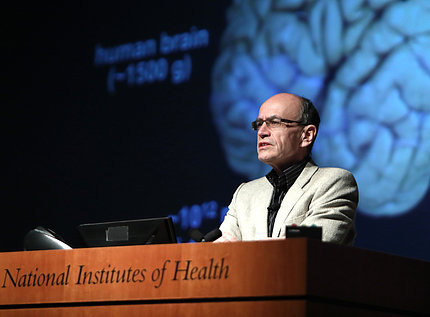 Dr. Südhof at podium in front of slide of human brain